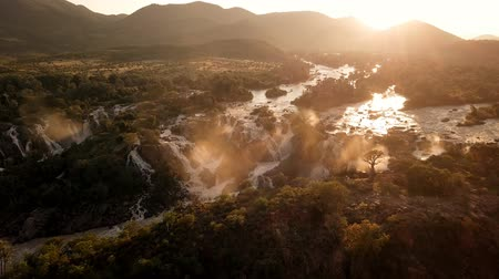 boulders : Sunrise in the waterfall of Epupa Falls on the Kunene River in Northern Namibia and Southern Angola. Aerial view from airplane.