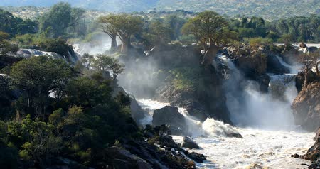 zuhatag : famous Epupa Falls on the Kunene River in Northern Namibia and Southern Angola border. Sunrise sunlight in water mist. This is africa. Beautiful landscape. Stock mozgókép