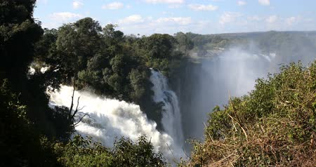 zimbabwe : Victoria falls after the rain season in May, the waterfall is full of water, everywhere is mist. Zambia Zimbabwe border, Africa wilderness landscape. Wonder of the World Stock Footage