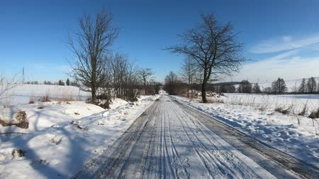 monte de neve : Car driving through the countryside in winter season, sunny day and landscape covered by snow, flat protune colors Stock Footage