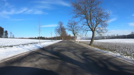 previously : Car driving through the countryside in winter season, sunny day and landscape covered by snow, flat protune colors Stock Footage