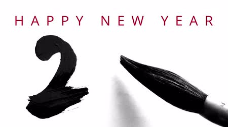hieróglifo : Happy New Year 2016 in English - writing calligraphy with a brush and thick ink with reflections - video greeting card with wishes Appearing on the top.