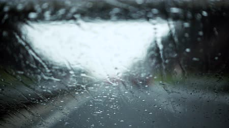 homályos : Rain drops splatters on windshield during rain storm, difficult driving conditions, out of focus