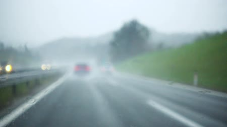 burza : Rain drops splatters on windshield during rain storm, difficult driving conditions, out of focus