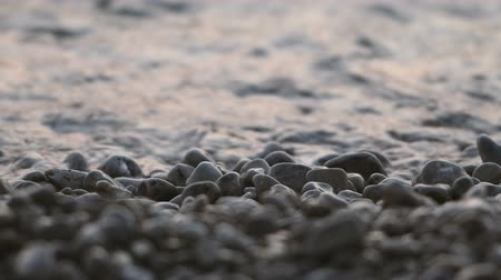 weathered : Close up of sea waves hitting pebbles on beach, selective focus