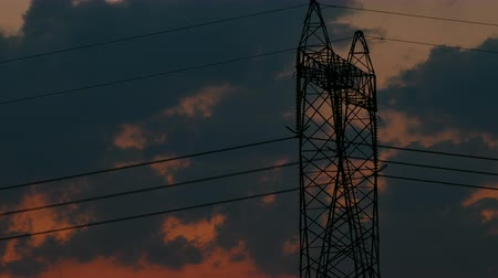 powerline : Silhouette of High voltage electric pylon, tower in sunset with clouds on the sky