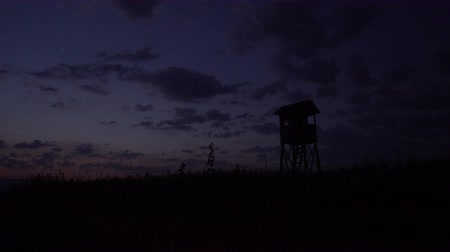 домик : Hunting tower, hide, lookout in dusk with cloudscape, corn field in front, clouds moving on dramatic sky