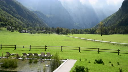 felhőtlen : Panoramic view in Logarska valley, Slovenia, green meadows with forest and high mountains in background, natural swimming pool with sunchairs in front Stock mozgókép