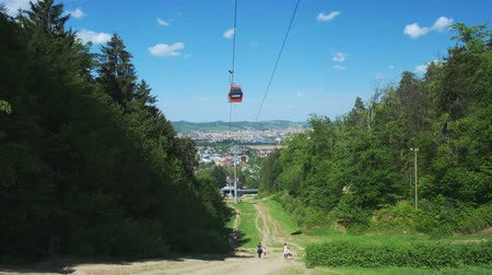 slovenya : Maribor, Slovenia - May 2, 2019: Pohorje cableway in Maribor, Slovenia with hikers walking beneath the cable cars on the popular hiking trail to Bellevue