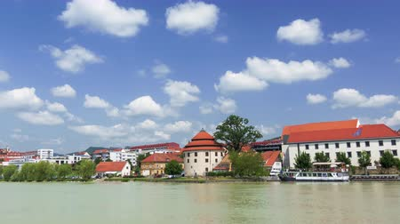 kostel : Maribor, Slovenia - June 16, 2019: Time lapse of clouds above small towns waterfront, Maribor, Slovenia, Lent district, pan from right to left, medieval buildings on the banks of Drava river