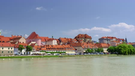architectural heritage : Maribor, Slovenia - June 16, 2019: Lent is the popular waterfront of Maribor, Slovenia, river with mediaeval town in background, time lapse pan left to right, buildings on the banks of a river, puffy clouds in the sky