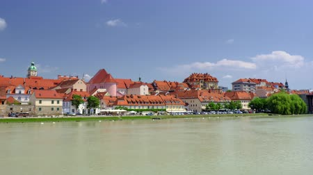 kostel : Maribor, Slovenia - June 16, 2019: Revealing view of Lent, the popular waterfront of Maribor, Slovenia with vintage architecture and street caffees it is popular with tourists and hosting the Lent festival Dostupné videozáznamy