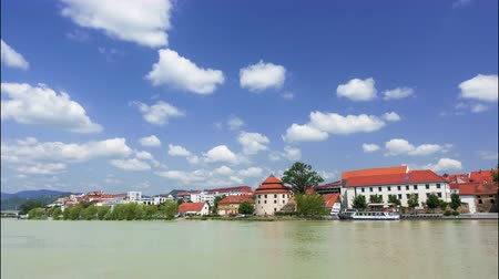 destinos de viagem : Maribor, Slovenia - June 16, 2019: White clouds on blue sky rolling above Lent promenade in Maribor, Slovenia, a river boat anchored near mediaeval watchtover, European towns waterfront Stock Footage