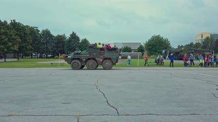 bojiště : Slovenska Bistrica, Slovenia - Sept 7, 2019: Children and visitors ride on armored personnel carrier Pandur put on display by Slovene armed forces at the doors open day.