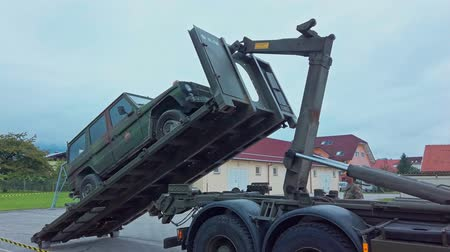 Slovenska Bistrica, Slovenia - Sept 7, 2019: Crane platform of recovery truck lifts a broken down military 4x4 all terrain vehicle. Battlefield recovery demonstration by Slovenias army Стоковые видеозаписи