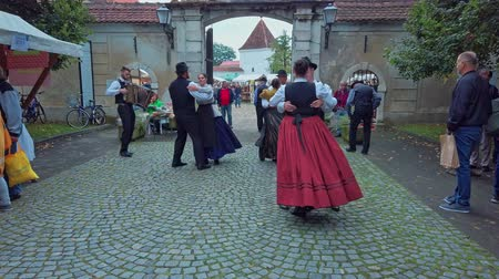 Slovneska Bistrica, Slovenia - Sept. 7 2019: Folklore dancers wearing national costumes perform traditional Slovene folk dance on street accompanied with accordeon player