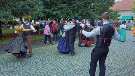 mercado : Slovneska Bistrica, Slovenia - Sept. 7 2019: Folklore dancers wearing national costumes perform traditional Slovene folk dance on street accompanied with accordeon player