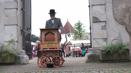 baixo ângulo : Slovenska Bistrica, Slovenia - Sept 7 2019: Vintage dressed man playing street organ at weekend fair in front of the castle gates in Slovenska Bistrica, Slovenia.