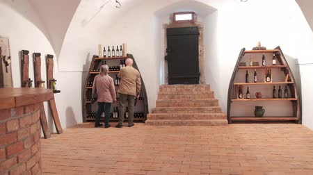 детали : Slovenska Bistrica, Slovenia - Sept 9 2019: Elderly couple pick bottles in wine cellar exhibition in Slovenska Bistrica castle