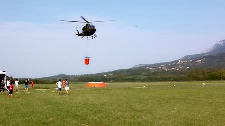 Ajdovscina, Slovenia - Aug 31 2019: Military helicopter of Slovene Air Force assisting local firefighters fighting a wildfire with a water bucket Стоковые видеозаписи