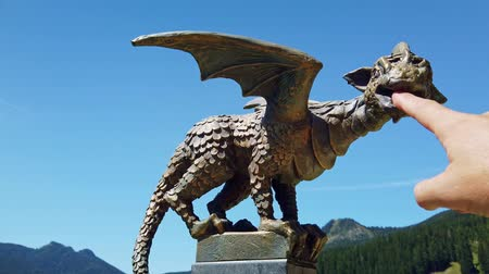 Solcava, August 17 2019: Male finger touches the bronze statue of the Lintver dragon, a signpost on the Solcava Panoramic road above Logar valley in Slovenia Stok Video