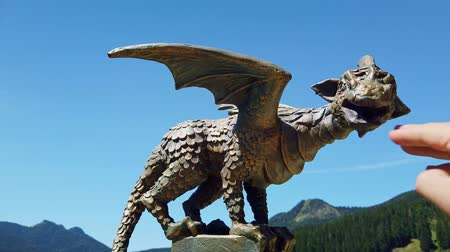 mitolojik : Solcava, August 17 2019: Bronze statue of the Lintver dragon, a signpost on the Solcava Panoramic road above Logar valley in Slovenia, a hand touching the dragon Stok Video