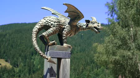 historical : Solcava, August 17 2019: Bronze statue of the Lintver dragon, a signpost on the Solcava Panoramic road above Logar valley in Slovenia Stock Footage