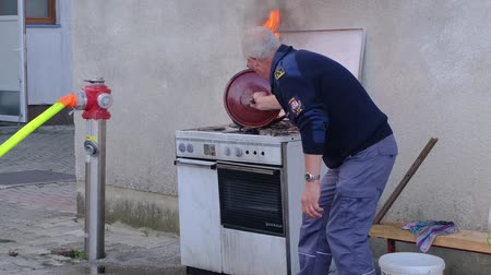 Slovenska Bistrica, Slovenia - Oct 4 2019: Firefighter demonstrates extinguishing a kitchen fire safely with a lid at public event at the fire station in Slovenska Bistrica, Slovenia Стоковые видеозаписи