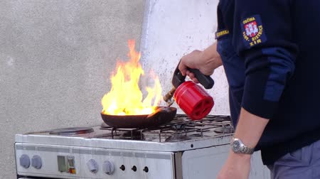 požár : Slovenska Bistrica, Slovenia - Oct 4 2019: Firefighter demonstrates the dangers of a kitchen fire and ignites pan with blow torch at public event at the fire station in Slovenska Bistrica, Slovenia