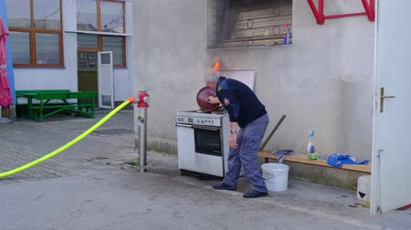 Slovenska Bistrica, Slovenia - Oct 4 2019: Firefighter demonstrates extinguishing a kitchen fire safely with a lid at public event at the fire station in Slovenska Bistrica, Slovenia Stok Video