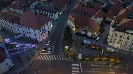crepúsculo : Slovenska Bistrica, Slovenia - Dec 25 2019: Christmas lights switch on in main square of small town Slovenska Bistrica, Slovenia, aerial time-lapse of Xmas market with decoration