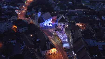 crepúsculo : Slovenska Bistrica, Slovenia - Dec 25 2019: Aerial view of Christmas fair on main square in Slovenska Bistrica, a small medieval town in Slovenia, cars pass by on main street
