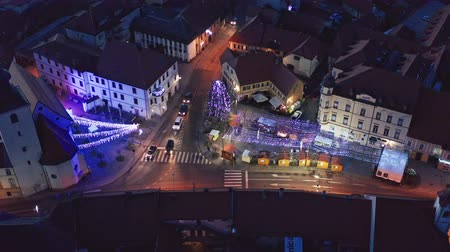historical : Slovenska Bistrica, Slovenia - Dec 25 2019: Aerial view of Christmas fair on main square in Slovenska Bistrica, a small medieval town in Slovenia, decorative lights illuminate the streets Stock Footage