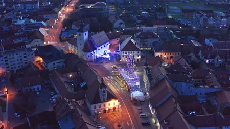 crepúsculo : Slovenska Bistrica, Slovenia - Dec 25 2019: Christmas fair on main square in Slovenska Bistrica, a small medieval town in Slovenia, aerial view of town center with shops and bright xmas lights Stock Footage