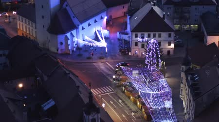 histórico : Slovenska Bistrica, Slovenia - Dec 25 2019: Aerial view of Christmas fair on main square in Slovenska Bistrica, a small medieval town in Slovenia, cars pass by on main street