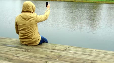 képek : man taking picture or shooting video with camera mobile phone or smartphone. Focus on water Stock mozgókép