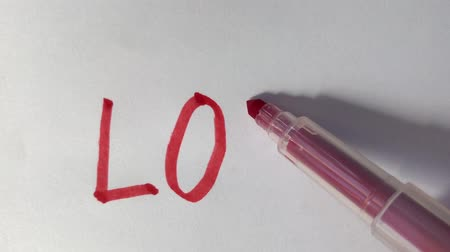 exercício : Artists draw a red a felt-tip pen, draw a word love on paper.