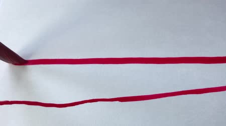 evidência : Artist paint with a brush, write a line on paper. Beautiful red watercolor on white paper.