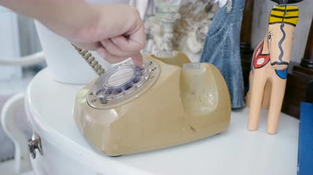 collectable : woman hand pick up old rotary style telephone on the table with vintage decorate style and dialing phone number. warm tone , retro style