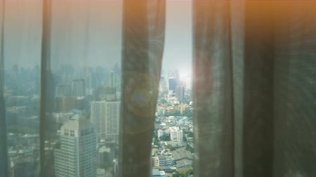 unveil : window curtain in room open for city view with wonderful lens flare effect in the evening
