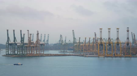 no exterior : 4K. Singapore shipping port with cargo ship sailing slowly on the sea and many container and yellow cranes in background Stock Footage
