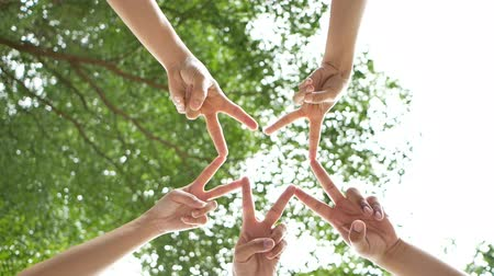 ingressou : low angle shot from below of a group of 5 young people place their hands together over sky and trees in the center of a circle. connection people together concept. 50fps