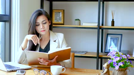 книжный магазин : 4K footage, beautiful Asian business woman sitting in front of computer laptop , reading and flip over note book page with thinking face at workspace in the morning , business people lifestyle. Стоковые видеозаписи