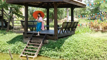 requintado : Asian woman wearing traditional Thai culture costume, vintage style with red umbrella walking to the river side pavilion, sit down and salute of respect (sawasdee).