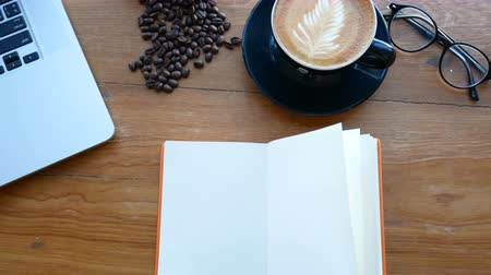 turn table : 4K. blank white book on wooden table, page flip from wind. book at work space with notebook , cup of coffee and glasses