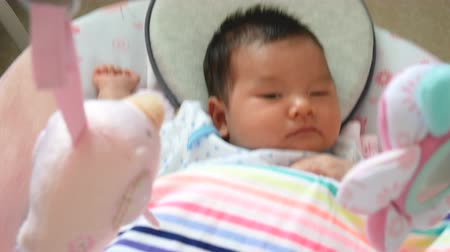 újszülött : 4K footage, adorable Asian baby feel sleepy , lying in a swing cradle Stock mozgókép