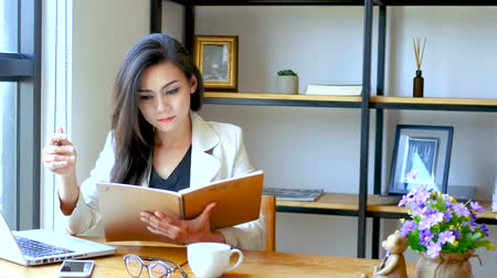 kávézó : 4K footage, beautiful Asian business woman sitting in front of computer laptop , reading and flip over note book page with thinking face at workspace in the morning , business people lifestyle. Stock mozgókép