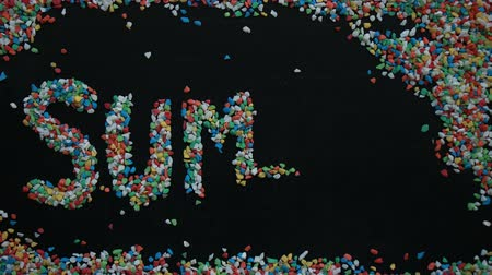 слово : 4K timelapse of SUMMER word made from colorful gravel on black chalk board Стоковые видеозаписи