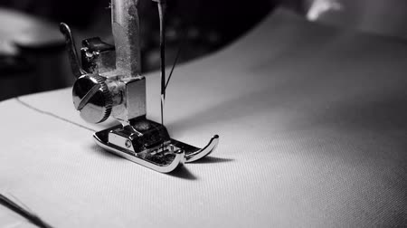 sewer : 4K footage. close up of sewing machine needle on white fabric with slow motion , black and white color Stock Footage