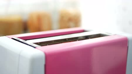 fél : 4K footage of toast bread popping out of pink toaster machine with good morning stamp on bread